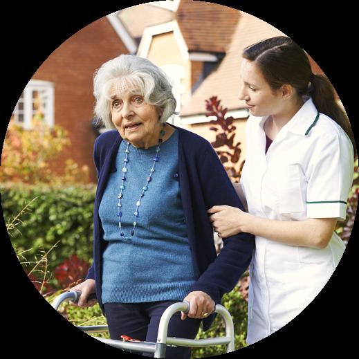 caregiver helping elderly woman to walk in the garden