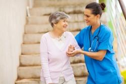 caregiver assisting an elderly woman