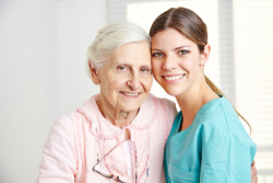 elderly woman with her caregiver smiling