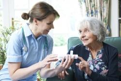 nures advising elderly woman on taking medication